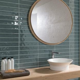 Esempio di una stanza da bagno design con ante in legno chiaro, piastrelle blu, piastrelle in ceramica, lavabo a bacinella, top in laminato e ante a filo
