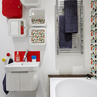 Design ideas for a small eclectic family bathroom in London with white cabinets, a built-in bath, white walls, vinyl flooring and a wall-mounted sink.