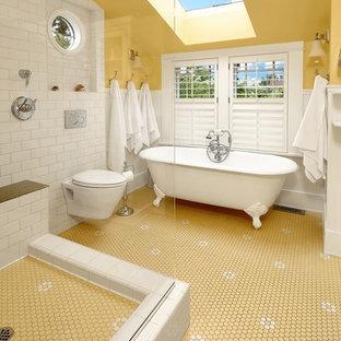 Идея дизайна: главная ванная комната среднего размера в викторианском стиле с белыми фасадами, ванной на ножках, открытым душем, инсталляцией, белой плиткой, плиткой кабанчик, желтыми стенами, полом из фанеры, разноцветным полом, открытым душем, консольной раковиной, столешницей из гранита и бежевой столешницей