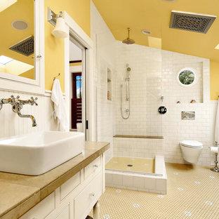 Cette photo montre une salle de bain principale victorienne de taille moyenne avec des portes de placard blanches, une baignoire sur pieds, une douche ouverte, un WC suspendu, un carrelage blanc, un carrelage métro, un mur jaune, un sol en contreplaqué, un plan vasque, un plan de toilette en granite, un sol multicolore, aucune cabine et un plan de toilette beige.