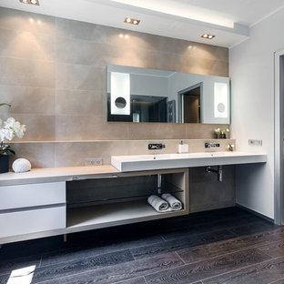 Inspiration för ett funkis badrum, med ett avlångt handfat, öppna hyllor, vita skåp, beige kakel, stenhäll, grå väggar och mörkt trägolv