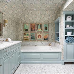 サンフランシスコの広いトラディショナルスタイルのおしゃれなマスターバスルーム (インセット扉のキャビネット、青いキャビネット、アンダーマウント型浴槽、マルチカラーの壁、大理石の床、アンダーカウンター洗面器、白い床、白い洗面カウンター、クロスの天井、壁紙) の写真