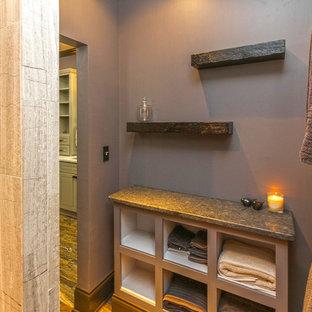 Imagen de cuarto de baño principal, de estilo americano, de tamaño medio, con armarios abiertos, puertas de armario con efecto envejecido, encimera de granito, baldosas y/o azulejos multicolor, baldosas y/o azulejos de piedra, paredes púrpuras y suelo de travertino
