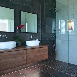 Ejemplo de cuarto de baño actual con armarios con paneles lisos, puertas de armario de madera oscura, ducha empotrada, baldosas y/o azulejos negros, baldosas y/o azulejos blancos, lavabo sobreencimera, encimera de madera, suelo negro y encimeras marrones