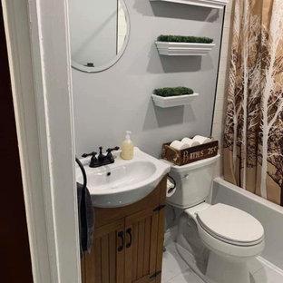 Kleines Uriges Duschbad mit Lamellenschränken, braunen Schränken, Eckbadewanne, Duschbadewanne, Wandtoilette mit Spülkasten, beigefarbenen Fliesen, Metrofliesen, grauer Wandfarbe, Sockelwaschbecken, Duschvorhang-Duschabtrennung, Einzelwaschbecken und freistehendem Waschtisch in Sonstige