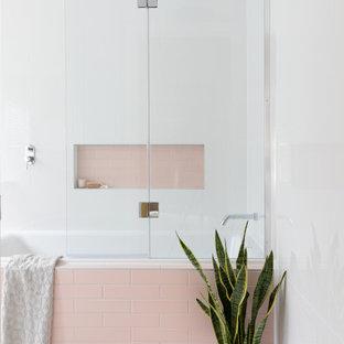 Идея дизайна: маленькая детская ванная комната в современном стиле с накладной ванной, душем над ванной, розовой плиткой, белыми стенами, серым полом и встроенной тумбой