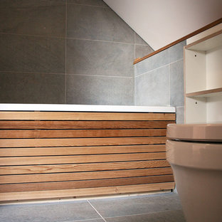 Design ideas for a small modern family bathroom in Other with open cabinets, wooden worktops, a built-in bath, a one-piece toilet, grey tiles, grey walls and porcelain flooring.