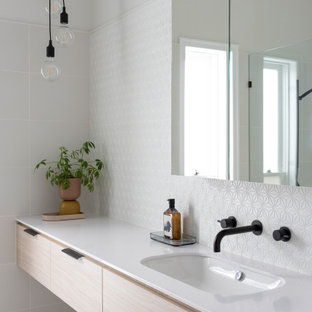This is an example of a large contemporary master bathroom in Melbourne with flat-panel cabinets, white tile, mosaic tile, white walls, ceramic floors, grey floor, a floating vanity, light wood cabinets, an undermount sink and white benchtops.