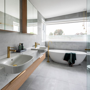Large contemporary master bathroom in Melbourne with flat-panel cabinets, a freestanding tub, white tile, ceramic floors, grey floor, grey benchtops, a double vanity, a floating vanity, medium wood cabinets, a drop-in sink and vaulted.