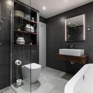 ロンドンの大きいモダンスタイルのおしゃれな浴室 (レイズドパネル扉のキャビネット、濃色木目調キャビネット、置き型浴槽、一体型トイレ、グレーのタイル、セメントタイル、グレーの壁、セラミックタイルの床、ペデスタルシンク、木製洗面台、オープン型シャワー、オープンシャワー、ブラウンの洗面カウンター) の写真