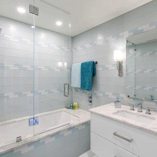 Esempio di una stanza da bagno contemporanea con ante lisce, ante bianche, vasca ad alcova, vasca/doccia, piastrelle blu, piastrelle di vetro, lavabo sottopiano, doccia aperta, top bianco, un lavabo e mobile bagno sospeso