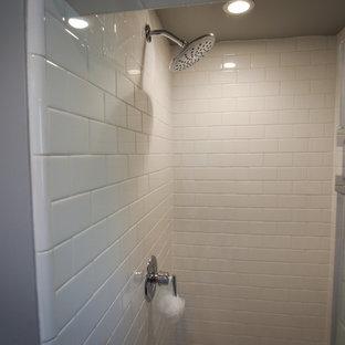 Kleines Modernes Duschbad mit Schrankfronten im Shaker-Stil, blauen Schränken, Eckdusche, Wandtoilette mit Spülkasten, weißen Fliesen, Porzellanfliesen, grauer Wandfarbe, Laminat, Unterbauwaschbecken, Quarzwerkstein-Waschtisch, braunem Boden, Falttür-Duschabtrennung und weißer Waschtischplatte in Los Angeles