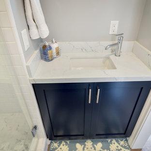 Aménagement d'une petit salle d'eau contemporaine avec un placard à porte shaker, des portes de placard bleues, une douche d'angle, un WC séparé, un carrelage blanc, des carreaux de porcelaine, un mur gris, sol en stratifié, un lavabo encastré, un plan de toilette en quartz modifié, un sol marron, une cabine de douche à porte battante et un plan de toilette blanc.