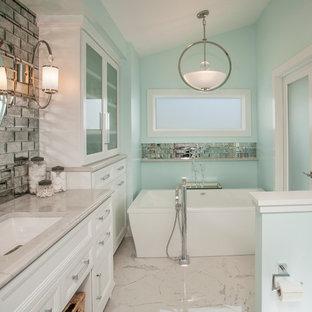 Diseño de cuarto de baño principal, contemporáneo, de tamaño medio, con armarios con paneles empotrados, puertas de armario blancas, bañera exenta, ducha empotrada, sanitario de una pieza, baldosas y/o azulejos grises, baldosas y/o azulejos con efecto espejo, paredes azules, suelo de mármol, lavabo bajoencimera y encimera de mármol
