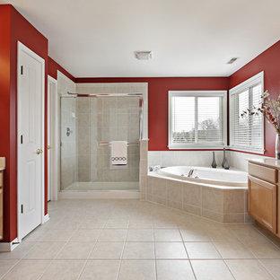 Foto di una grande stanza da bagno tradizionale con ante con bugna sagomata, ante in legno chiaro, top in superficie solida, vasca ad angolo, piastrelle beige, piastrelle in gres porcellanato, pareti rosse, pavimento in gres porcellanato e lavabo sottopiano