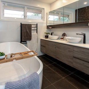 Mid-sized contemporary bathroom in Sydney with flat-panel cabinets, medium wood cabinets, a freestanding tub, white tile, ceramic tile, white walls, porcelain floors, a vessel sink, engineered quartz benchtops, grey floor and white benchtops.