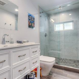 Ispirazione per una stanza da bagno con doccia classica di medie dimensioni con ante bianche, pareti bianche, pavimento marrone, porta doccia scorrevole, ante con riquadro incassato, doccia alcova, WC monopezzo, piastrelle grigie, piastrelle di cemento, lavabo sottopiano, top in marmo e pavimento in laminato