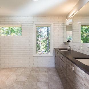 На фото: большие главные ванные комнаты в стиле модернизм с плоскими фасадами, темными деревянными фасадами, открытым душем, унитазом-моноблоком, белой плиткой, керамогранитной плиткой, серыми стенами, полом из керамогранита, врезной раковиной и столешницей из талькохлорита