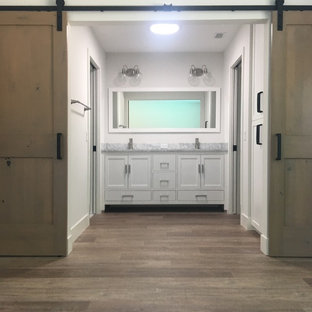 Inspiration for a mid-sized 1960s master white tile and subway tile laminate floor and brown floor alcove shower remodel in Los Angeles with shaker cabinets, white cabinets, a one-piece toilet, gray walls, an undermount sink, marble countertops and a hinged shower door