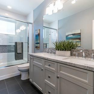 Idéer för att renovera ett mellanstort vintage grå grått badrum, med grå skåp, ett badkar i en alkov, en dusch/badkar-kombination, grå väggar, ett undermonterad handfat, svart golv, dusch med skjutdörr, luckor med infälld panel, en toalettstol med separat cisternkåpa, vit kakel, tunnelbanekakel, klinkergolv i porslin och marmorbänkskiva