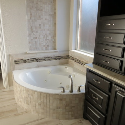 Inspiration for a large timeless master beige tile and porcelain tile porcelain tile bathroom remodel in Dallas with raised-panel cabinets, black cabinets, white walls, solid surface countertops and an undermount sink