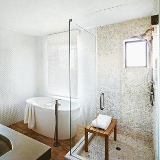 Bild på ett funkis badrum, med ett fristående badkar, en hörndusch, vit kakel, vita väggar, kakel i småsten och klinkergolv i småsten