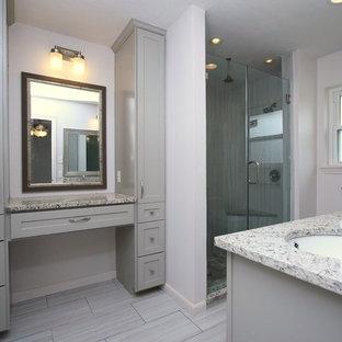 Klassisk inredning av ett mellanstort en-suite badrum, med skåp i shakerstil, grå skåp, en toalettstol med separat cisternkåpa, grå kakel, porslinskakel, grå väggar, klinkergolv i porslin, ett undermonterad handfat, granitbänkskiva och en hörndusch