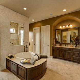 Идея дизайна: огромная главная ванная комната в средиземноморском стиле с врезной раковиной, фасадами с утопленной филенкой, темными деревянными фасадами, мраморной столешницей, двойным душем, унитазом-моноблоком, бежевой плиткой, каменной плиткой, коричневыми стенами, полом из травертина и накладной ванной