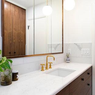 オマハの小さいコンテンポラリースタイルのおしゃれな浴室 (フラットパネル扉のキャビネット、濃色木目調キャビネット、ドロップイン型浴槽、シャワー付き浴槽、一体型トイレ、白いタイル、磁器タイル、白い壁、磁器タイルの床、アンダーカウンター洗面器、珪岩の洗面台、白い床、シャワーカーテン、白い洗面カウンター) の写真