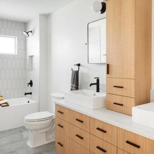 ミネアポリスの中くらいのコンテンポラリースタイルのおしゃれな子供用バスルーム (フラットパネル扉のキャビネット、淡色木目調キャビネット、アルコーブ型浴槽、分離型トイレ、白いタイル、セラミックタイル、白い壁、セラミックタイルの床、ベッセル式洗面器、クオーツストーンの洗面台、グレーの床、白い洗面カウンター、ニッチ、洗面台2つ、シャワー付き浴槽、オープンシャワー、フローティング洗面台) の写真