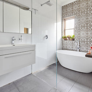 Mid-sized contemporary master wet room bathroom in Sydney with white cabinets, a freestanding tub, a wall-mount toilet, ceramic tile, white walls, ceramic floors, grey floor, an open shower, flat-panel cabinets, brown tile and a console sink.