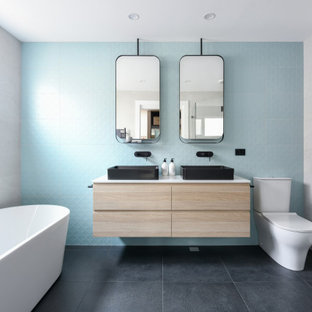 Photo of a mid-sized contemporary bathroom in Sydney with flat-panel cabinets, light wood cabinets, a freestanding tub, a two-piece toilet, blue tile, white tile, a vessel sink, black floor, white benchtops, a double vanity and a floating vanity.