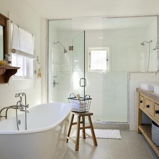 Maritim inredning av ett badrum, med ett nedsänkt handfat, gula skåp, ett fristående badkar och en dusch i en alkov