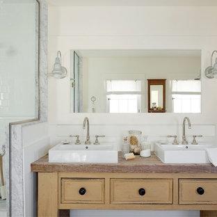 Bild på ett maritimt badrum, med ett fristående handfat, möbel-liknande, beige skåp, en dusch i en alkov, vit kakel och tunnelbanekakel