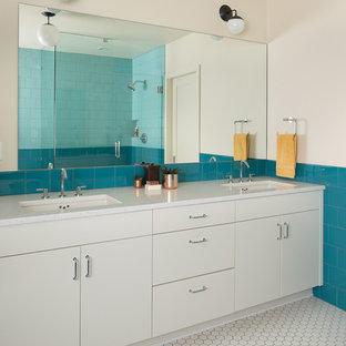 Modelo de cuarto de baño principal, minimalista, grande, con armarios con paneles lisos, puertas de armario blancas, bañera encastrada, ducha esquinera, baldosas y/o azulejos azules, baldosas y/o azulejos de porcelana, paredes blancas, suelo de baldosas de porcelana, lavabo bajoencimera, encimera de vidrio reciclado, suelo blanco y ducha con puerta con bisagras