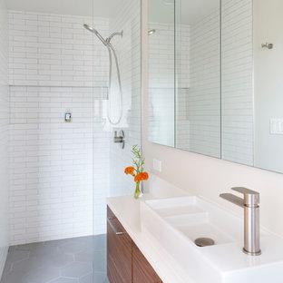 50 tals inredning av ett litet en-suite badrum, med släta luckor, skåp i mellenmörkt trä, en kantlös dusch, en vägghängd toalettstol, vit kakel, keramikplattor, vita väggar, mellanmörkt trägolv, ett fristående handfat, bänkskiva i kvarts och med dusch som är öppen