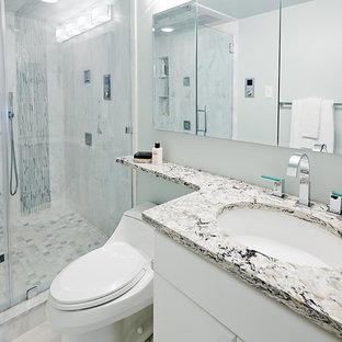 Exempel på ett mellanstort modernt badrum med dusch, med luckor med upphöjd panel, vita skåp, en dusch i en alkov, blå kakel, vit kakel, stickkakel, grå väggar, ett undermonterad handfat, granitbänkskiva och dusch med gångjärnsdörr