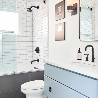 Bathroom - mid-sized contemporary master white tile and subway tile ceramic tile, white floor and single-sink bathroom idea in Chicago with white walls, blue cabinets, granite countertops, flat-panel cabinets, an undermount sink, white countertops, a freestanding vanity and a two-piece toilet