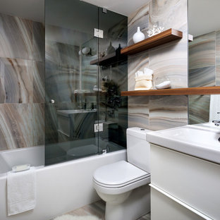 Design ideas for a medium sized contemporary bathroom in Toronto with an integrated sink, flat-panel cabinets, white cabinets, an alcove bath, a shower/bath combination, multi-coloured tiles and a two-piece toilet.