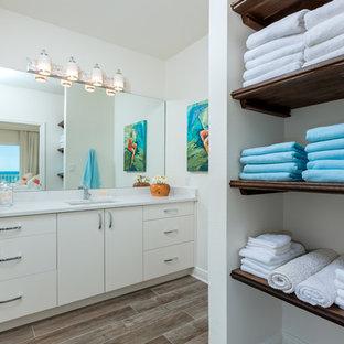 Réalisation d'une salle d'eau marine de taille moyenne avec un placard à porte plane, des portes de placard blanches, un mur blanc, un sol en bois brun, un lavabo encastré, un plan de toilette en surface solide et un sol marron.