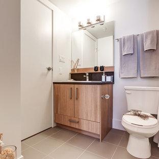 Kleines Skandinavisches Badezimmer mit flächenbündigen Schrankfronten, hellbraunen Holzschränken, Toilette mit Aufsatzspülkasten, schwarzen Fliesen, lila Wandfarbe, Keramikboden, Quarzwerkstein-Waschtisch und beigem Boden in Calgary