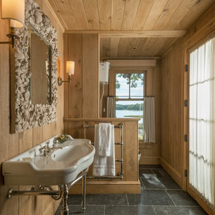 Small mountain style master ceramic floor and black floor bathroom photo in New York with brown walls and a console sink