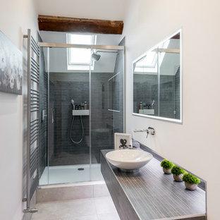 Foto di una piccola stanza da bagno padronale minimal con doccia a filo pavimento, WC sospeso, pareti beige, pavimento in gres porcellanato, lavabo a bacinella, top piastrellato, pavimento grigio, porta doccia scorrevole e top grigio