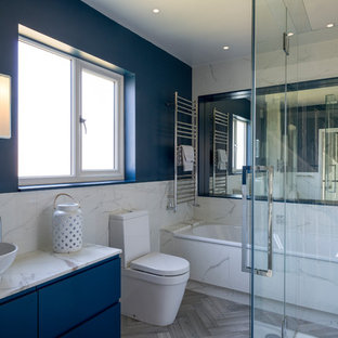 This is an example of a medium sized contemporary ensuite bathroom in London with flat-panel cabinets, blue cabinets, an alcove bath, a two-piece toilet, marble tiles, blue walls, a vessel sink, marble worktops, grey floors, white worktops and white tiles.