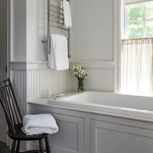 Example of a mid-sized country master slate floor and brown floor alcove bathtub design in Bridgeport with shaker cabinets, white cabinets and white walls