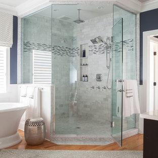 Foto de cuarto de baño principal, tradicional, grande, con bañera exenta, baldosas y/o azulejos blancos, paredes azules, suelo de madera en tonos medios, ducha esquinera y baldosas y/o azulejos de cemento