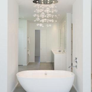 Modern inredning av ett stort en-suite badrum, med släta luckor, bänkskiva i akrylsten, ett fristående badkar, vit kakel, glasskiva, grå skåp, en öppen dusch, en toalettstol med hel cisternkåpa, vita väggar, laminatgolv, ett integrerad handfat, beiget golv och med dusch som är öppen