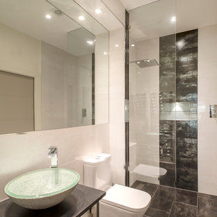 Inspiration for a small contemporary bathroom in London with a vessel sink, a built-in shower, a two-piece toilet, beige walls and black and white tiles.