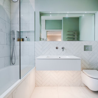 This is an example of a medium sized contemporary shower room bathroom in London with flat-panel cabinets, white cabinets, an alcove shower, a wall mounted toilet, white tiles, porcelain tiles, green walls, porcelain flooring, an integrated sink, white floors and white worktops.