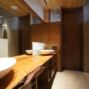 Example of a large trendy master beige tile and stone tile limestone floor alcove shower design in Miami with a vessel sink, flat-panel cabinets, medium tone wood cabinets, wood countertops, brown walls and brown countertops